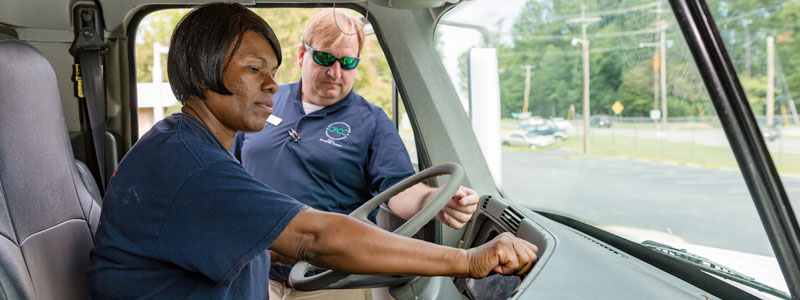 CDL student Vanessa Jackson behind wheel of truck with instructor