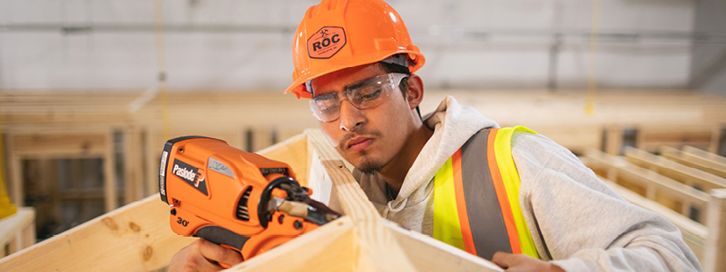 man working with drill on construction site, wearing hard hat with the ROC logo