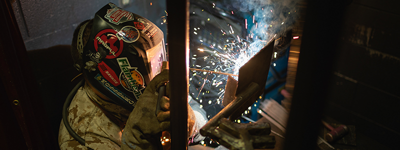 student in welding mask making sparks as he welds
